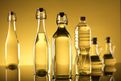 Rapeseed oil concept. Vegetable oil made from rapeseed in bottles on glass table Royalty Free Stock Photo