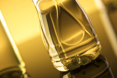 Rapeseed oil concept. Vegetable oil made from rapeseed in bottles on glass table Stock Photos