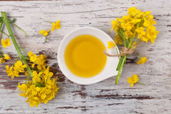 Rapeseed oil and flower. Rapeseed oil and flowers on wooden background, top view Royalty Free Stock Photo