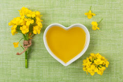 Rapeseed oil and flower. Rapeseed oil in heart shaped bowl and flowers on green background, top view Royalty Free Stock Image