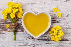 Rapeseed oil and flower. Rapeseed oil in heart shaped bowl and flowers on wooden background, top view Royalty Free Stock Photos