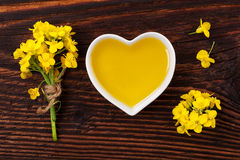 Rapeseed oil and flower. Rapeseed oil in heart shaped bowl and flowers on wooden background, top view Stock Images