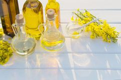 Rapeseed oil and rape flowers on wooden table Stock Photography