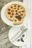 Rapiécez la tarte avec les tomates-cerises, le fromage et les oignons du plat blanc Image libre de droits