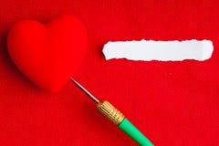 Rapiécez le coeur vide de papier de copyspace avec le dard sur le textile rouge de tissu Image libre de droits