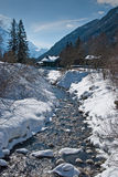 Rapid brook running by snowcapped banks. Rapid brook running among snowcapped banks under alpine slope, near wooden houses Royalty Free Stock Photo