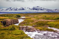 The rapid cold creek. Flows among the flat tundra. On the horizon - rhyolite mountains in the snow.  The concept of extreme northern tourism stock photos