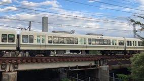 Rapid express train in Osaka, Japan. A rapid express train crosses a bridge amid a web of power lines in Osaka city, Japan stock video