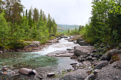 Rapid river flow in mountains Stock Image