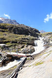 Rapid stream, bridge and mountain panorama, Hohe Tauern Alps, Austria Royalty Free Stock Images