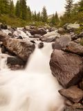 Rapid stream flowing down over stones  Blurred waves of stream running over boulders and stones, high water level after rains Royalty Free Stock Photography