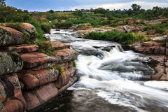 Rapid stream. Rapidly flowing river among granite rocks and foliage Royalty Free Stock Image