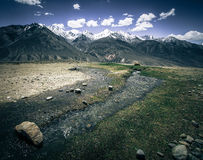 The rapid stream in the valley and snow-capped peaks of the moun. Tains. Tajikistan. Toned Stock Image