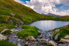 Rapid streams flow to lake Capra in mountains. Fagaras mountain ridge under the gorgeous cloudscape in the distance. Beautiful summer landscape of Romania Royalty Free Stock Photos