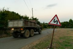 Rapid truck on the mountain road. Dangerous roads. Wooden area, road sign. Image royalty free stock images