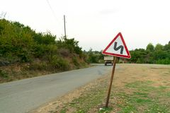Rapid truck on the mountain road. Dangerous roads. Wooden area, road sign. Image stock images
