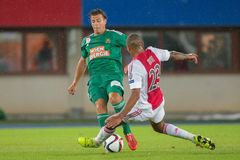 Rapid vs. Ajax. VIENNA, AUSTRIA - JULY 29, 2015: Stefan Schwab (SK Rapid) and Kenny Tete (Ajax) fight for the ball in an UEFA Champions League qualification game royalty free stock images