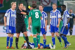 Rapid vs. Helsinki. VIENNA, AUSTRIA - AUGUST 28, 2014: Referee Stephane Laurent Lannoy (France) shows the yellow card to Stefan Schwab (#8 Rapid) in an UEFA Royalty Free Stock Image