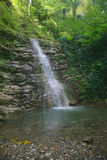 Rapid waterfall in the mountains. The water is collected in depressions of the rocks overgrown. swirling waterfall. Krasnodar Krai. Very nice Stock Photography
