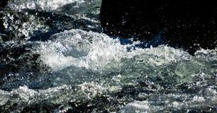 Rapide faisante rage de rivière éclaboussant contre une roche photo stock