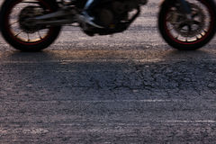 Rapidly riding a motorcycle on the road Stock Images