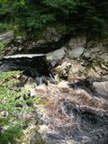 Rapids and dark amber coloured water Findhorn River at Randolphs Leap, Morayshire, Scotland, UK. Stock Image