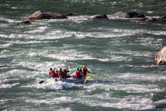 In the rapids of the Ganges. A dinghy is just crossing the rapids of the Ganges at Rishikesh, India. Unrecognizable persons royalty free stock images