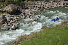 Rapids in a mountain river in Nepal. Foreign tourists go through a set of rapids in a mountain river in Nepal. Rafting is a popular sport for foreign tourists Royalty Free Stock Photos