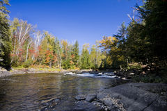 Rapids and river Northern Ontario. A set of rapids in a small river . Taken on a bright sunny fall day, with blue skies and beginnings of fall colour Royalty Free Stock Photos