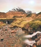 Rapids in small waterfall on stream, Higland in Scotland an early spring day. Snowy mountain peaks Stock Image