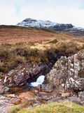Rapids in small waterfall on stream, Higland in Scotland an early spring day. Snowy mountain peaks Royalty Free Stock Images
