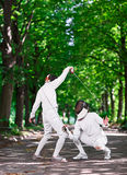Rapier fencers women fencing over park alley Stock Photography