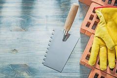 Rappa handskar för säkerhet för röda tegelstenar för murslev på den wood brädebricklaen Royaltyfri Foto