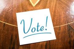 Rappel de vote sur le papier se trouvant sur le placard en bois Image stock