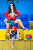 Rapper attitude rap singer hip Hop Dancer. Performing. Stylish women and little boy posing holding their feet on ball at basketball court Royalty Free Stock Images