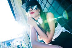 Rapper girl with headphones in a european city Stock Images