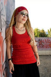 Rapper girl posing at sprayed wall. Hip-hop chick posing at the graffiti sprayed wall outdoors Royalty Free Stock Photography