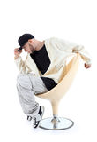Rapper sitzt auf Stuhl und hält Blendenschutzkappe Stockbilder