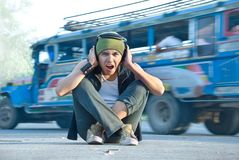 Rapper in street traffic covering ears. Young Hispanic rapper dude in casual grunge clothing with cap and headphone sitting on the street midst jeepney traffic Stock Photo