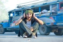 Rapper in street traffic covering ears stock photo