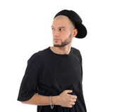 Rapper wearing black t-shirt and hat looks into distance Stock Photo