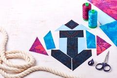 Rappezzatura di cucito dell'ancora del blocco, bobine dei fili, tessuti, bugia della corda sulla superficie di bianco Fotografia Stock Libera da Diritti