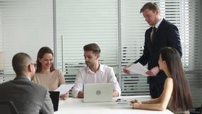 Rapport de papier masculin de présentation de directeur donnant le plan d'action aux employés banque de vidéos