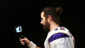 Rapporti del giocatore di football americano alle reti sociali facendo uso di uno smartphone stock footage