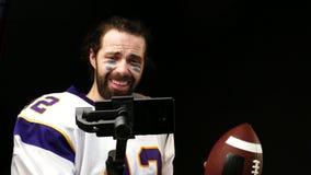 Rapporti del giocatore di football americano alle reti sociali facendo uso di uno smartphone archivi video