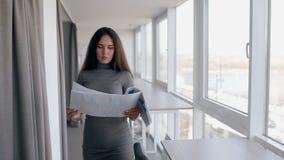 Rapporto finanziario leggente della giovane venditora della donna di affari che va in tutto il corridoio luminoso archivi video