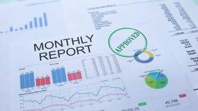 Rapporto mensile approvato, mano che timbra guarnizione sul documento ufficiale, statistiche video d archivio