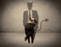 Rappresentante che affronta la sua propria ombra del diavolo Fotografie Stock Libere da Diritti