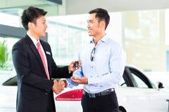 Rappresentante di automobile asiatico che vende auto al cliente immagini stock