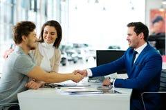 Rappresentante e cliente che stringono le mani che si congratulano alla sala d'esposizione di gestione commerciale immagine stock